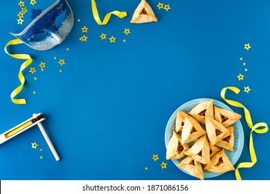 Purim celebration concept (jewish carnival holiday) on blue background, top view, copy space. Flat lay with hamantaschen cookies and  mask. - Shutterstock ID 1871086156