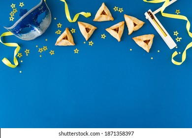 Purim celebration concept (jewish carnival holiday) on blue background, top view, copy space. Flat lay with hamantaschen cookies and  mask. - Shutterstock ID 1871358397