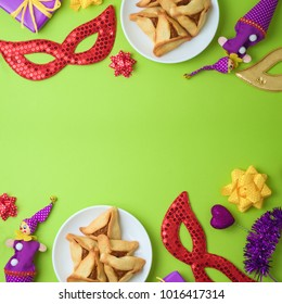 Purim holiday background with carnival mask and hamantaschen cookies. Top view