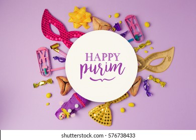 Purim holiday concept with white paper circle and party supplies on purple background. Top view from above