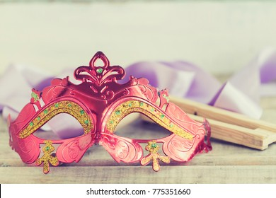 Purim jewish holiday composition with purim mask and purim gragger or a noisemaker on a vintage wood background with copys pace