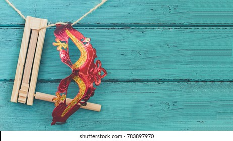 Purim jewish holiday composition with purim mask and purim gragger or a noisemaker hanging on a rope against a vintage wood green background with copy space