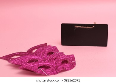Purim masks and black board isolated pink background