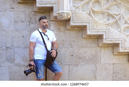 Puritan male photographer dressed in summer white t shirt is holding a camera and a bag.Tourism concept.