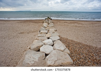 purneck stone rocks make a groyne leading through the beach to the sea with isle of wight on the horizon