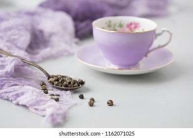 Purple Adderley Fine Bone China Cup and Saucer with Spoon of Herbal Tea beside on Grey Background