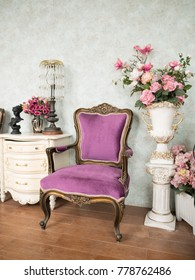 Purple armchair in white room and has a lot of multi color of flowers. Sweet vintage room full of flowers