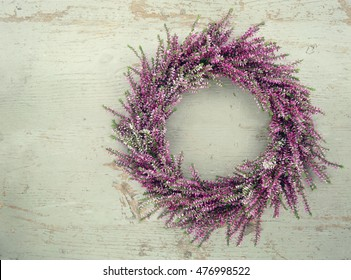 Purple autumn heather flower wreath on green wooden vintage background with copy space