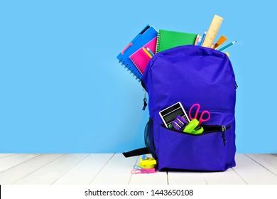 Sac à dos violet rempli de fournitures scolaires sur fond bleu. Retour à l'école. Copier l'espace.