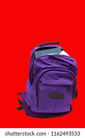 Purple backpack on red with books sticking out