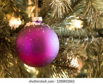 Purple balls with snowflakes on pine tree outdoors