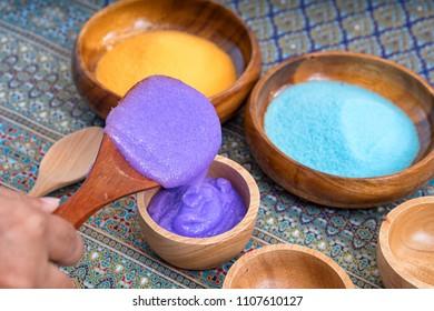 Purple bath salt for spa on wooden spoon.