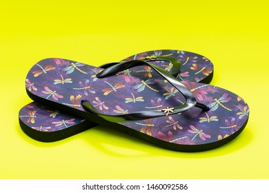 Purple Beach Day Flip Flops with dragonfly pattern isolated on bright yellow background.