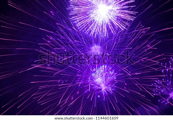 Purple and blue fireworks in the night sky. Violet festive firecracker. Beautiful background