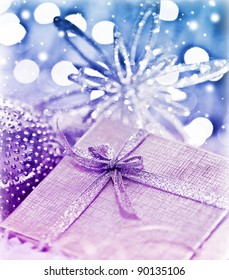 Purple blue gift box with baubles decorations, Christmas tree ornament for winter holidays, present with abstract bokeh shiny glowing blur lights background