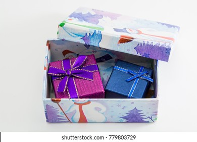 Purple and blue gift boxes decorated with ribbon bows inside the box with a Christmas pattern.