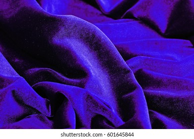 Purple blue Velvet dress material cloth texture pattern.  tailoring stitching concept. Shiny beautiful fashion fabric. Shiny clothing material sample.Creased fabric.