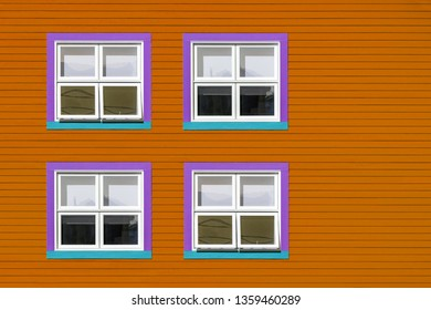 Purple, blue and white windows on a orange wooden wall. Minimalism style of the houses of Iles de la Magdalen, Canada, in bright colours with space for text.