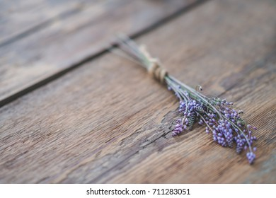 Purple bouquet tied with hemp rope on wooden background