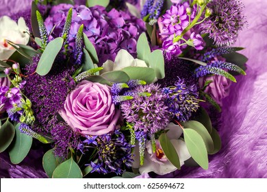 Purple bouquet with a variety of colors. Roses, hydrangeas, lilacs, greens, leaves, orchids. Background of flowers