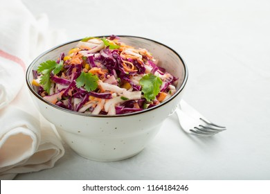 Purple cabbage and carrot salad with mayonnaise in a white bowl on a light background. Classic coleslaw. Diet vegetarian dish. Copy space