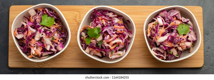 Purple cabbage and carrot salad with mayonnaise in a white bowl on a black background. Set of three classic coleslaw salad. Diet vegetarian dish. Top view