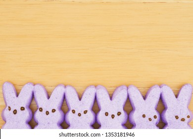 Purple candy bunnies on textured wood background with copy space for your Easter message