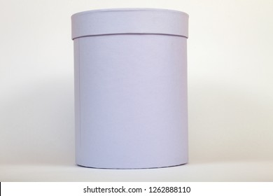 A purple cardboard box of a tube close up on a white background of a round shape with a closed lid for gift wrapping or storing flowers, a surprise, or a package in shopping stores upon purchase.
