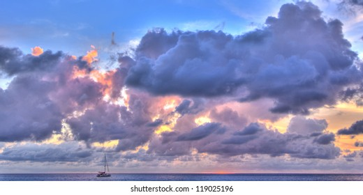 Purple cast panorama of sunset in ocean with yacht