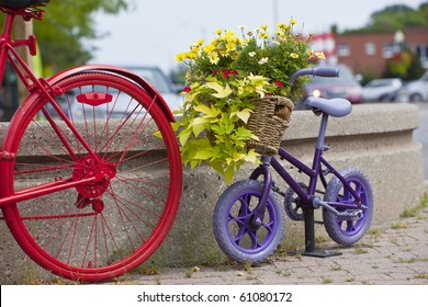 Purple child's bike behind an adult's bike as decoration
