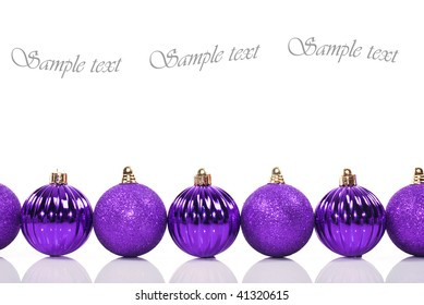 Purple christmas baubles on a white background with space for text