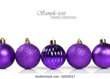 Purple christmas baubles on white background with space for text