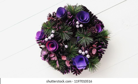 Purple Christmas Wreath on White Wooden Background, Top View, Flat Lay, Winter Holidays Concept.