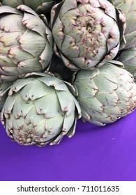 Purple cloth and green artichokes