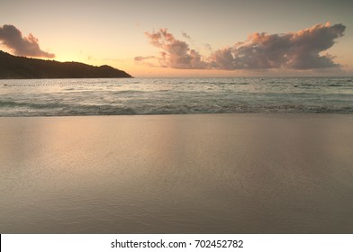 Purple clouds reflected on the surface of a white sand beach in the Seychelles Islands, Africa, during sunset, where the water acts as a mirror for the beautiful sky
