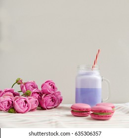 Purple coffee in stylized mason jar cup with macarons and roses and colorful decoration. Blueberry milk shake, cocktaill, frappuccino. Unicorn coffee. Unicorn food