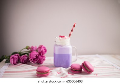 Purple coffee in stylized mason jar cup with macarons and roses and colorful decoration. Blueberry milk shake. Unicorn coffee. Unicorn food