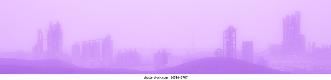 Purple colored cement factory on the horizon in the desert