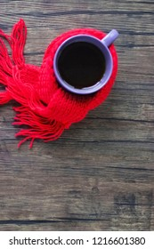 Purple cup with black tea, coffee or hot chocolate in  red scarf on  brown wooden background. The concept of home comfort in the cold season. Hugge.