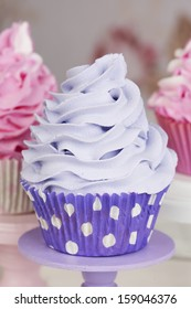 Purple cupcake with pink cupcakes in the background