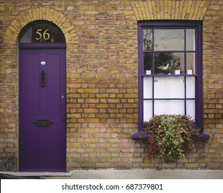 Purple door and window of a Victorian house in London (UK). July 2017.