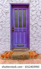 Purple Door with Worn Rug and Venetian Stucco Textured Wall