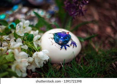 Purple dragon or lizard is hatching from the egg. Surrounded by the green grass and white blossoms.
