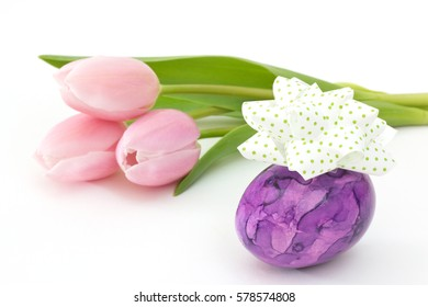 Purple Easter egg with bow near pink tulips on white background