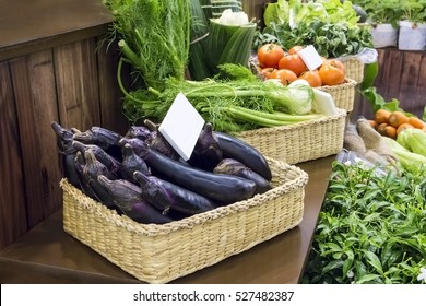 Purple eggplant and various vegetables in baskets on sales at farmer market display exhibition.