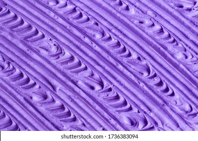 Purple facial cream (alginate face mask, body wrap, hair conditioner) texture close up, selective focus. Lavender abstract background with brush strokes.