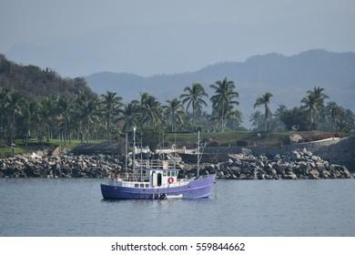 A purple fishing trawler anchored in Manzanillo Bay, Colima, Mexico.