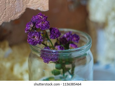 Purple flaccid flower in a glass jar on the background of a broken window sill