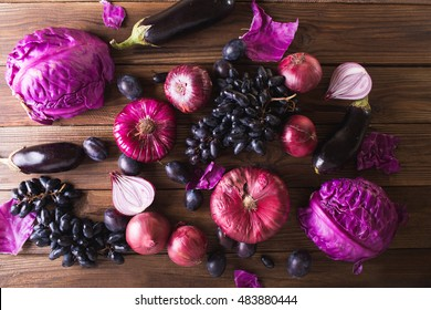 Purple fruits and vegetables on a wooden background.