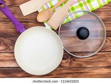 Purple frying pan with glass lid, kitchen wooden utensil and towel on the wooden table. Top view. Cooking meal.